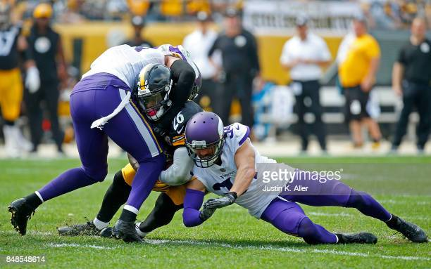 Le'Veon Bell of the Pittsburgh Steelers is tackled by Anthony Barr and Andrew Sendejo of the Minnesota Vikings in the second half during the game at...
