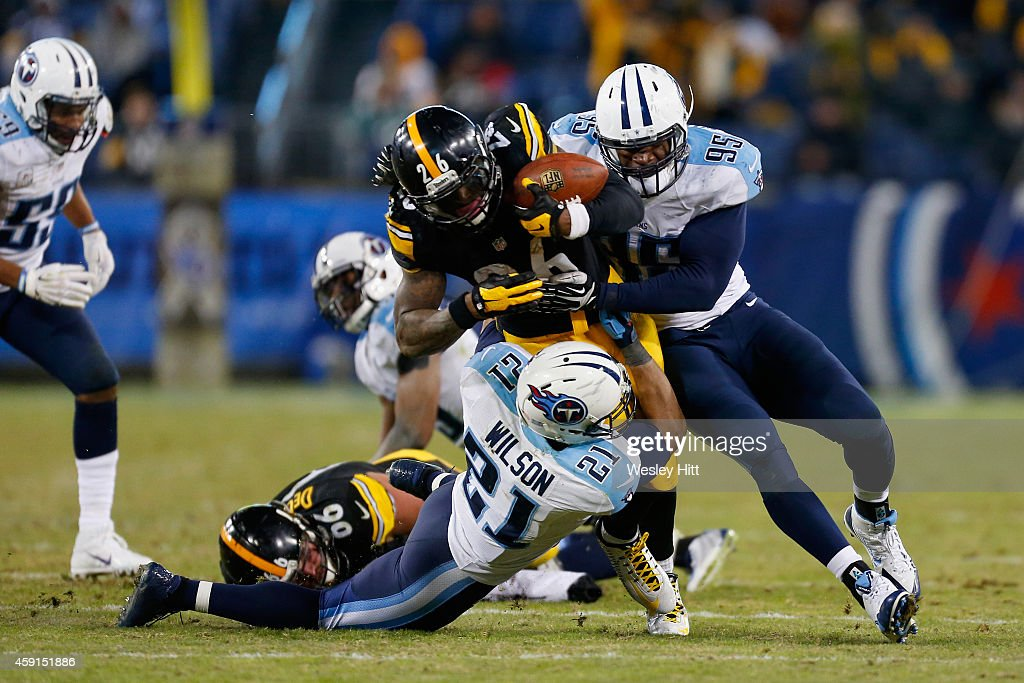 Le'Veon Bell #26 of the Pittsburgh Steelers is tackled by George Wilson #21 and Kamerion Wimbley #95 of the Tennessee Titans in the fourth quarter at LP Field on November 17, 2014 in Nashville, Tennessee. The Pittsburgh Steelers won 27-24.