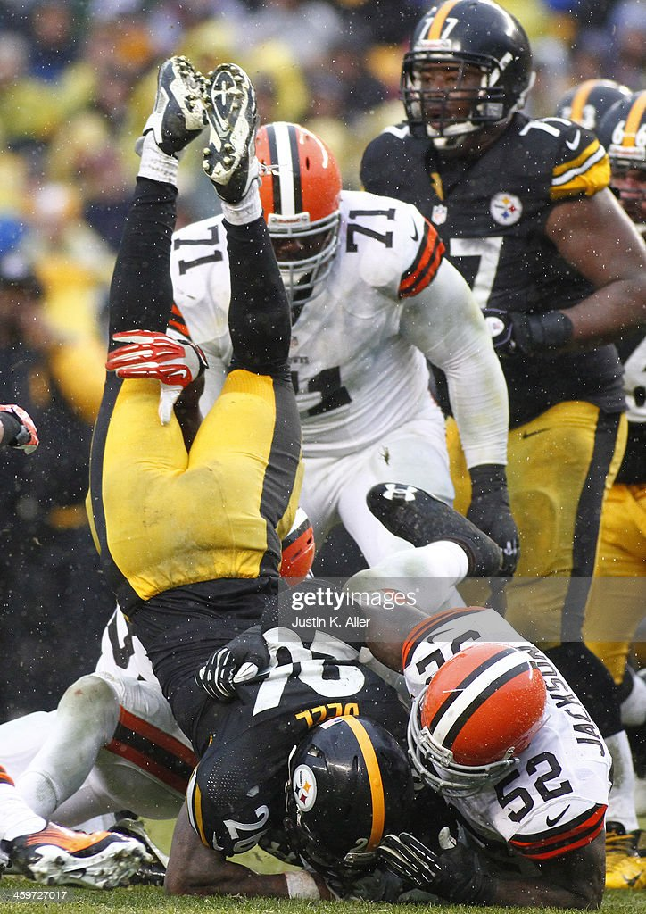 Le'Veon Bell #26 of the Pittsburgh Steelers is up ended while rushing against the Cleveland Browns during the game on December 29, 2013 at Heinz Field in Pittsburgh, Pennsylvania.