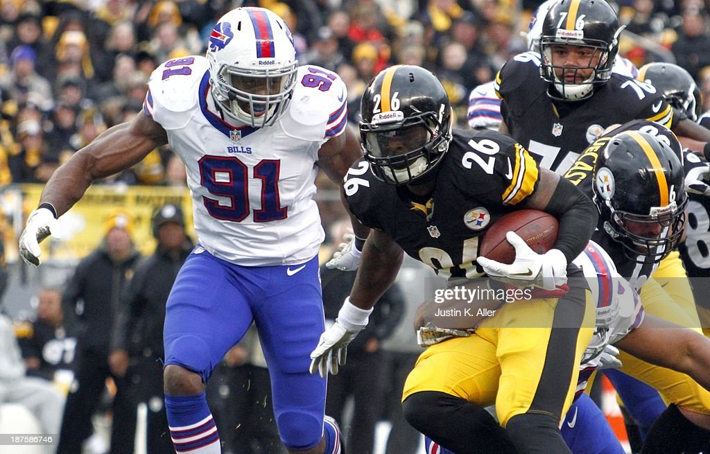 Le'Veon Bell #26 of the Pittsburgh Steelers rushes against Manny Lawson #91 of the Buffalo Bills during the game on November 10, 2013 at Heinz Field in Pittsburgh, Pennsylvania.
