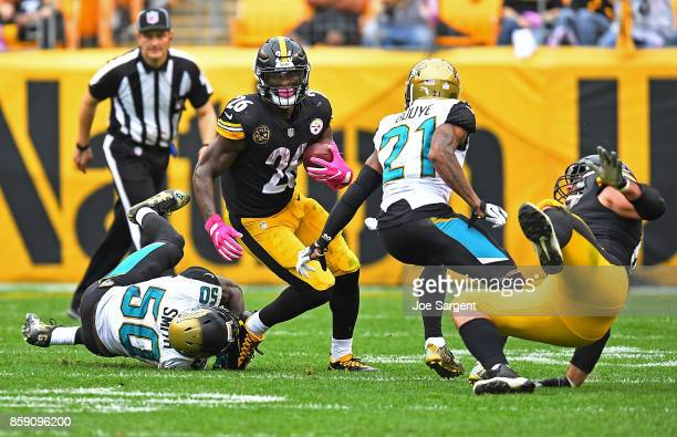 Le'Veon Bell of the Pittsburgh Steelers rushes against Telvin Smith of the Jacksonville Jaguars and AJ Bouye in the second half during the game at...