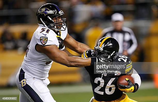Le'Veon Bell of the Pittsburgh Steelers tries to break a tackle by Daryl Smith of the Baltimore Ravens during the first quarter at Heinz Field on...