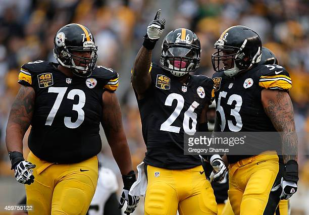 Le'Veon Bell reacts alongside Ramon Foster and Maurkice Pouncey of the Pittsburgh Steelers after picking up a first down during the first quarter...