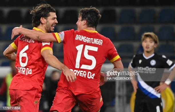 Leverkusen's Austrian defender Aleksandar Dragovic celebrates with Leverkusen's Austrian midflielder Julian Baumgartlinger scoring during the German...