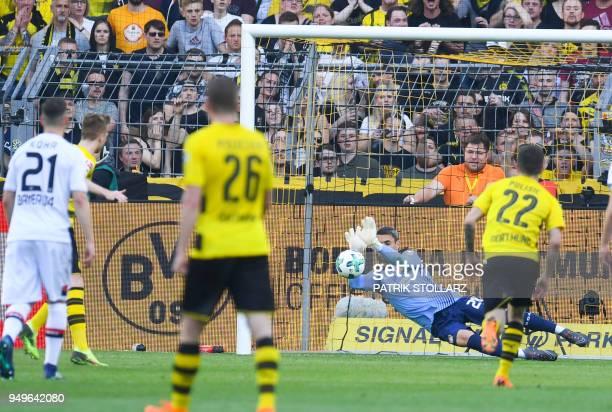 Leverkusen's Austrian goalkeeper Ramazan Oezcan holds a penalty shot by Dortmund's German forward Marco Reus during the German first division...