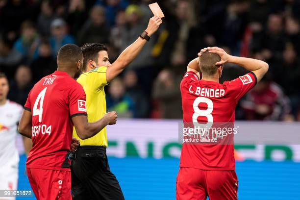 Leverkusen's Benjamin Henrichs receives the red card from referee Harm Osmers during the Bundesliga soccer match between Bayer Leverkusen and RB...