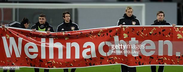 Leverkusen's Finnish head coach Sami Hyypiä holds a banner reading 'Christmas' after the German first division Bundesliga football match Bayer...