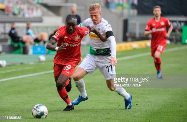 Leverkusen's French forward Moussa Diaby and Moenchengladbach's Swedish defender Oscar Wendt vie for the ball during the German first division...