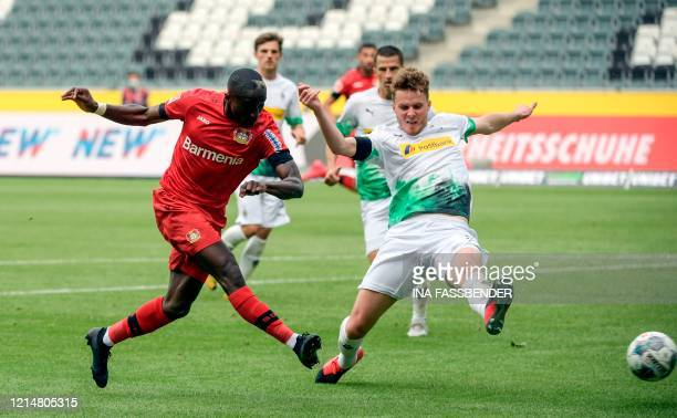 Leverkusen's French forward Moussa Diaby and Moenchengladbach's Swiss defender Nico Elvedi vie for the ball during the German first division...