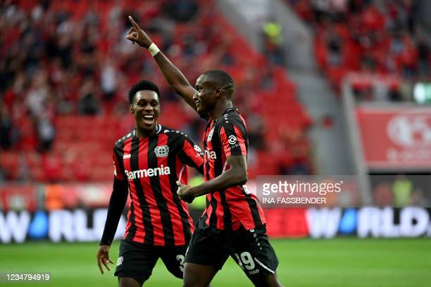 Leverkusen's French forward Moussa Diaby celebrates with Leverkusen's Dutch defender Jeremie Frimpong after scoring the 3-0 during the German first...