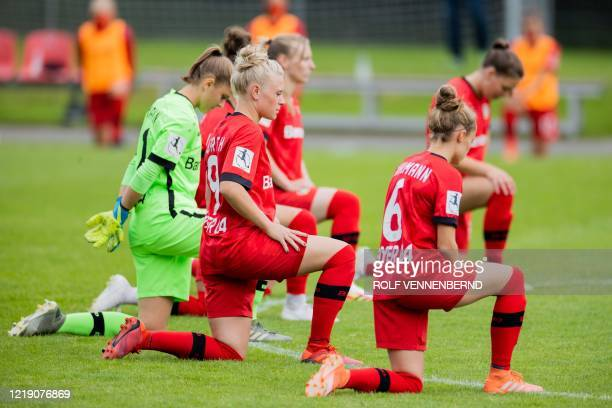 Leverkusen's German defender Merle Barth , Leverkusen's German defender Henrike Sahlmann and their teammates take a knee in solidarity with protests...