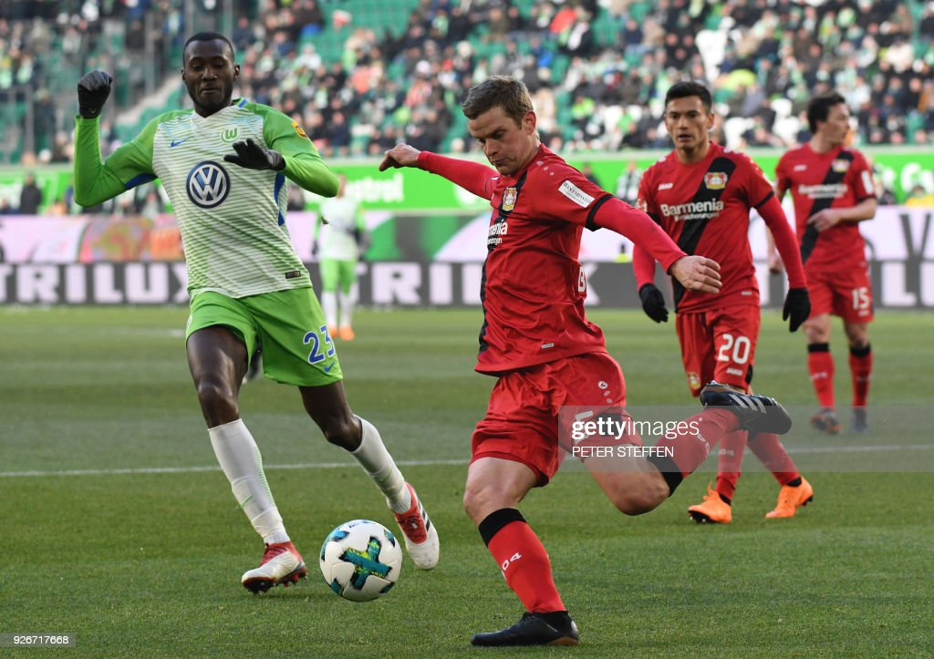 Leverkusen's German defender Sven Bender (C) shoots the ball as Wolfsburg's French midfielder Josuha Guilavogui (L) tries to block during the German first division Bundesliga football match VfL Wolfsburg vs Bayer Leverkusen in Wolfsburg, northern Germany, on March 3, 2018. / AFP PHOTO / dpa / Peter Steffen / Germany OUT