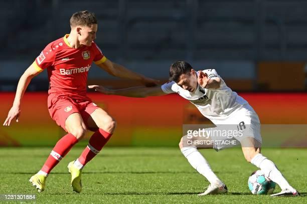 Leverkusen's German forward Florian Wirtz and Augsburg's Slovakian midfielder Laszlo Benes vie for the ball during the German first division...