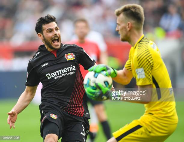 Leverkusen's German forward Kevin Volland and Frankfurt's Finnish goalkeeper Lukas Hradecky vie for the ball during the German first division...