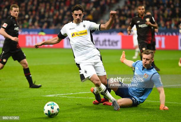 Leverkusen's German goalkeeper Bernd Leno and Moenchengladbach's German forward Lars Stindl vie for the ball during the German first division...