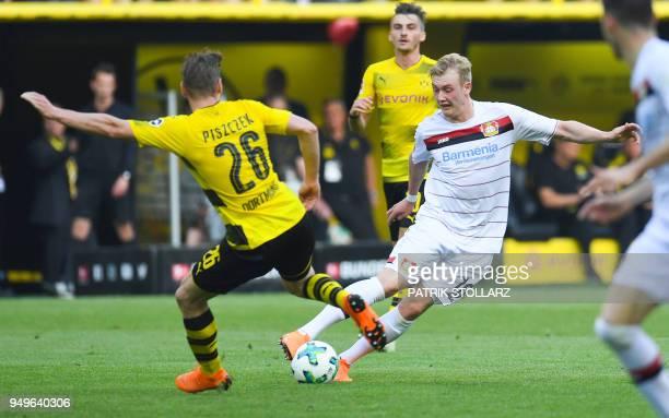 Leverkusen's German midfielder Julian Brandt and Dortmund's Polish defender Lukasz Piszczek vie for the ball during the German first division...
