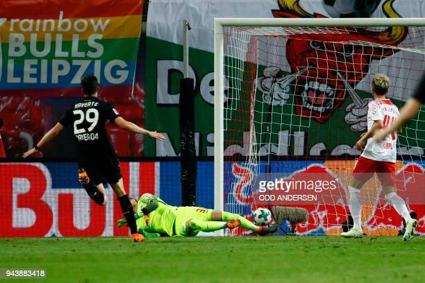 Leverkusen's German midfielder Kai Havertz scores in front of Leipzig's Hungarian goalkeeper Peter Gulacsi during the German first division...