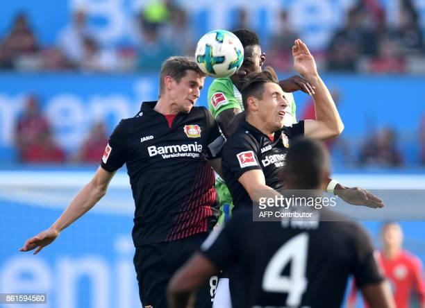 Leverkusen's German midfielder Lars Bender and Leverkusen's German midfielder Dominik Kohr vie for the ball with Wolfsburg's French midfielder Josuha...