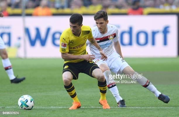 Leverkusen's Greek defender Panagiotis Retsos and Dortmund's US midfielder Christian Pulisic vie for the ball during the German first division...