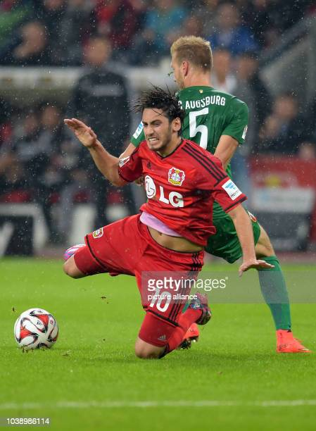 Leverkusen's Hakan Calhanoglu and Augsburg's Ragnar Klavan fight for the ball during the Bundesliga Day 5 soccer match between Bayer 04 Leverkusen...