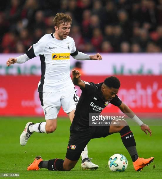 Leverkusen's Jamaican midfielder Leon Bailey and Moenchengladbach's German midfielder Christoph Kramer vie for the ball during the German first...