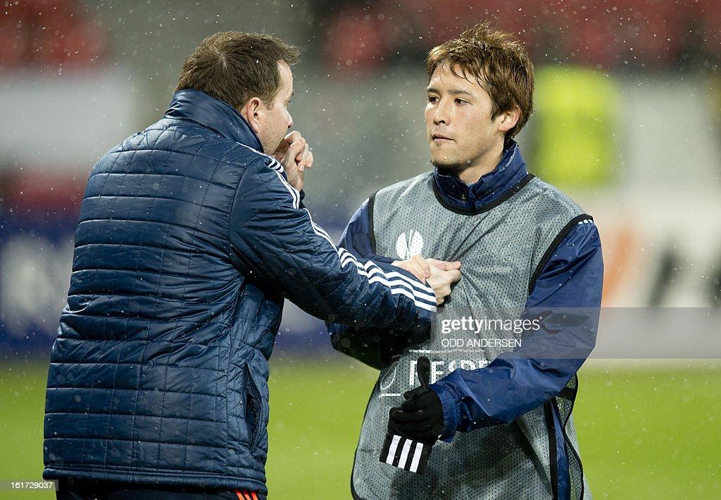 Leverkusen's Japanese midfielder Hajime Hosogai (R) is given instructions by an unidentified staff member prior to the UEFA Europa League football match Bayer 04 Leverkusen vs SL Benfica on February 14, 2013 in Leverkusen, western Germany. Benfica defeated Leverkusen 1-0.