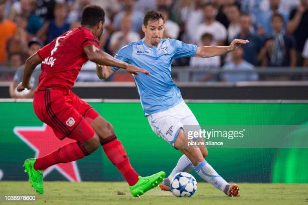 Leverkusen's Jonathan Glao Tah ) and Rome's Miroslav Klose in action during the UEFA Champions League play-off round first leg soccer match between...