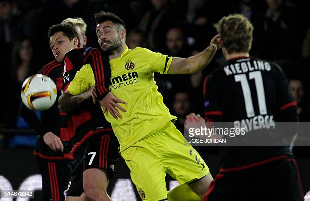 Leverkusen's Mexican forward Chicharito vies with Villarreal's defender Mario during the UEFA Europa League Round of 16 first leg football match...