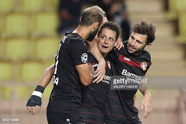 Leverkusen's Mexican forward Javier Hernández Balcázar is congratulated by teammates after scoring a goal during the UEFA Champions League football...