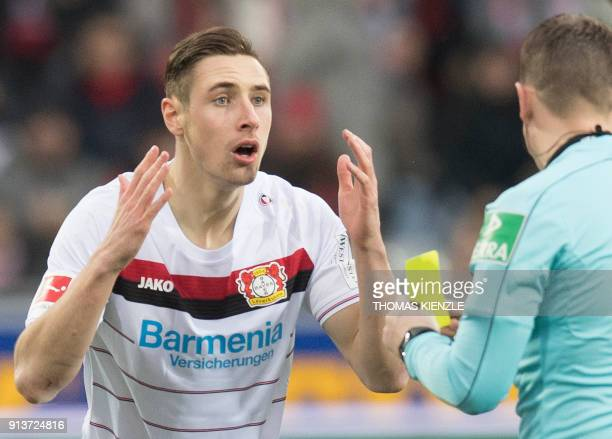 Leverkusen's midfielder Dominik Kohr reacts as referee Robert Kampka shows the yellow card during the German first division Bundesliga football match...