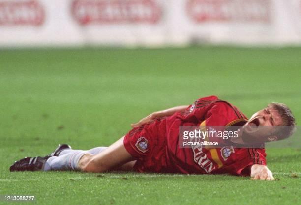 Leverkusens slowakischer AbwehrspielerVratislav Gresko faßt sich, verletzt am Boden liegend, mit schmerzverzerrtem Gesicht an den Oberschenkel -...