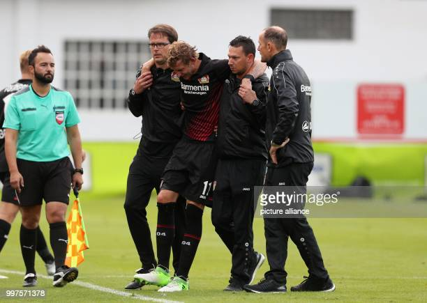 Leverkusen's Stefan Kießling leaves the pitch injured supported by head coach Heiko Herrlich during the soccer friendly between Bayer Leverkusen and...