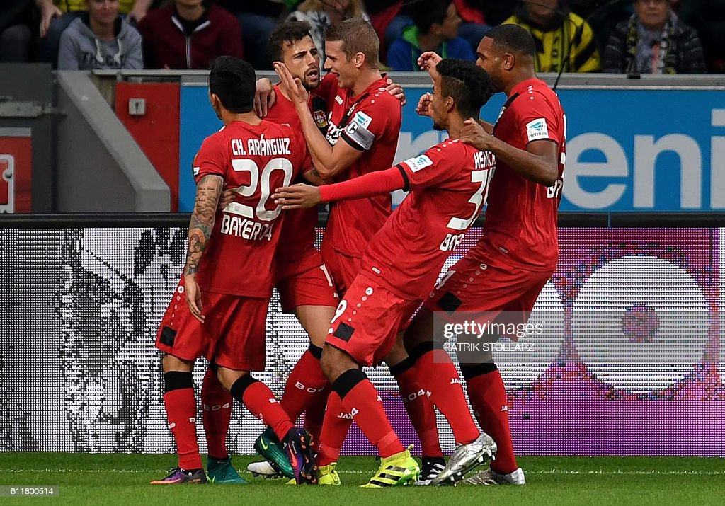 Leverkusen's Swiss forward Admir Mehmedi (2nd L) and his teammates celebrate after scoring during the German first division Bundesliga football match between Bayer 04 Leverkusen and BVB Borussia Dortmund in the Bay Arena in Leverkusen, western Germany on October 1, 2016. / AFP / PATRIK