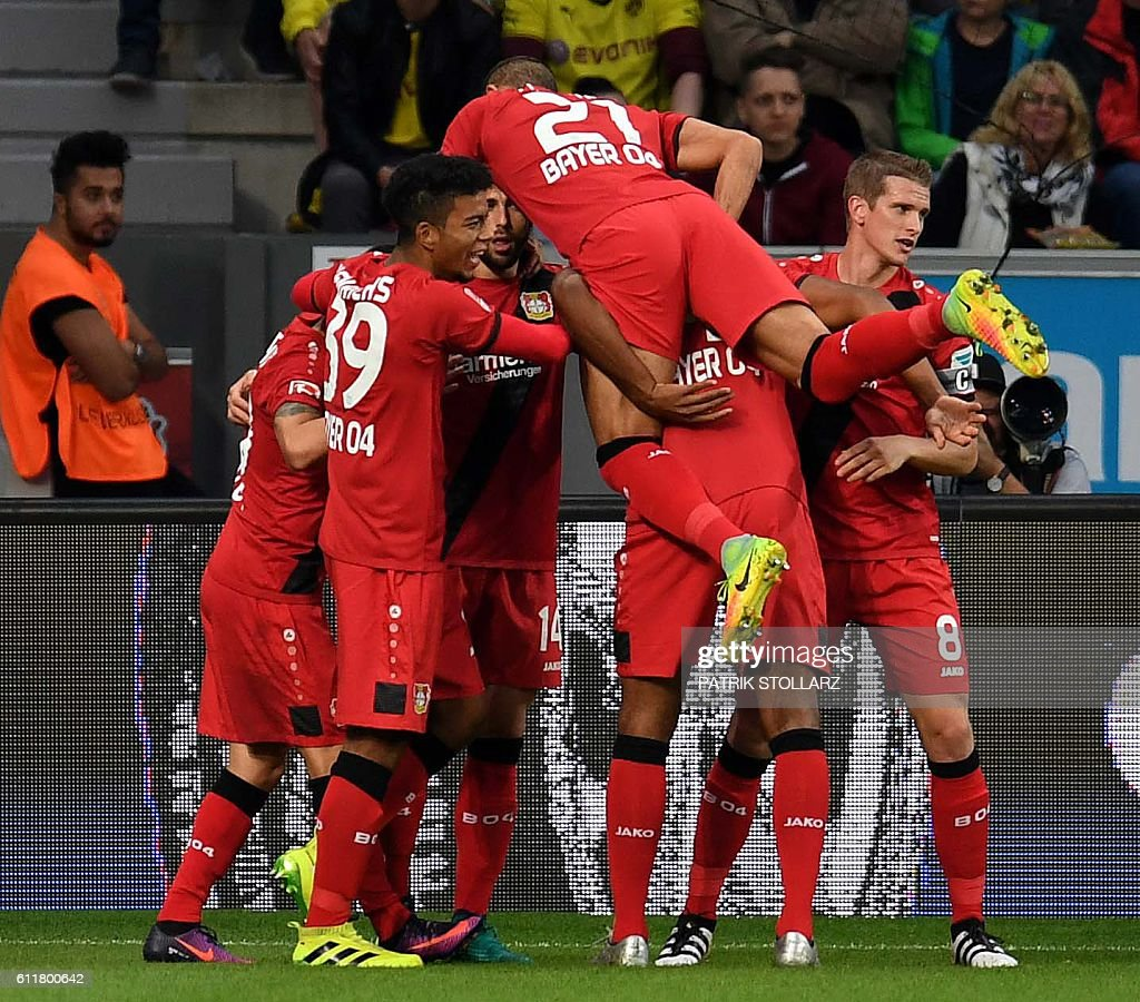 Leverkusen's Swiss forward Admir Mehmedi (C) and his teammates celebrate after scoring during the German first division Bundesliga football match between Bayer 04 Leverkusen and BVB Borussia Dortmund in the Bay Arena in Leverkusen, western Germany on October 1, 2016. / AFP / PATRIK