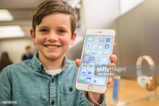 Levi aged 10 shows of the new iPhone 6s Plus in rose gold as crowds wait in anticipation for the release of the iPhone 6s and 6s Plus at Apple Store...