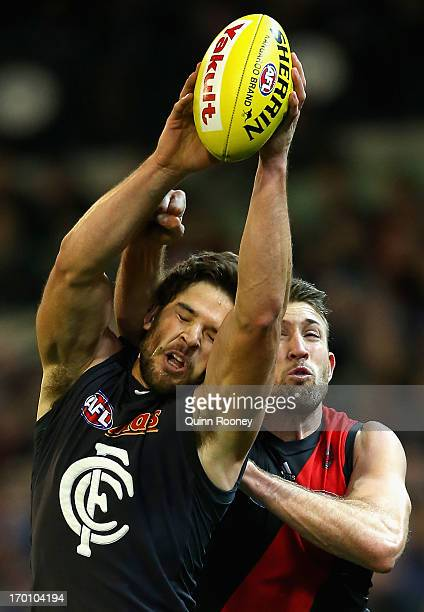 Levi Casboult of the Blues marks infront of Cale Hooker of the Bombers during the round 11 AFL match between the Essendon Bombers and the Carlton...