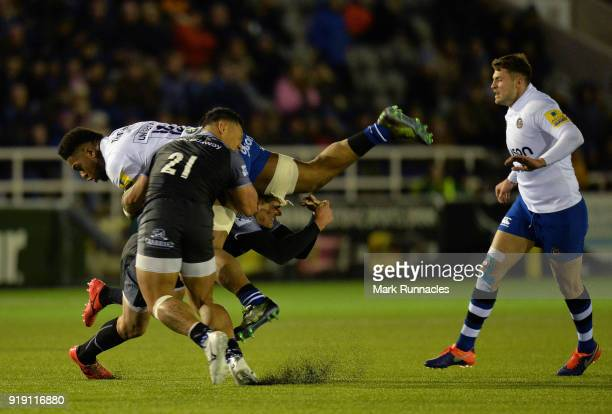 Levi Douglas of Bath Rugby is tackled by Toby Flood and Sonatane Takulua of Newcastle Falcons during the Aviva Premiership match between Newcastle...