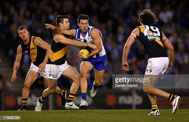 Levi Greenwood of the Kangaroos breaks a tackle during the round 15 AFL match between the North Melbourne Kangaroos and the Richmond Tigers at Etihad...