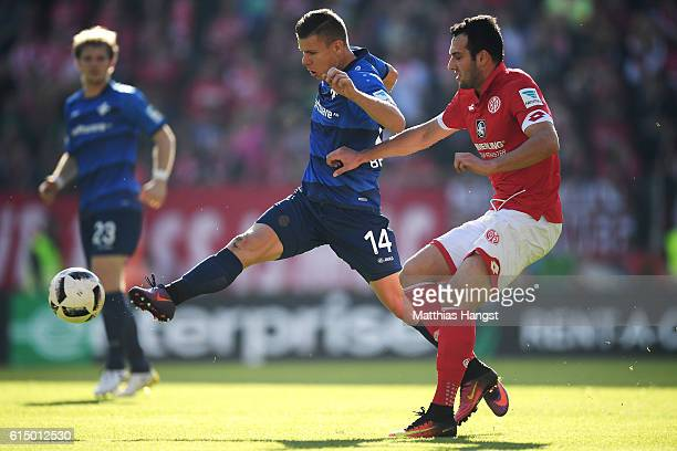Levin Oeztunali of Mainz and Roman Bezjak of Darmstadt battle for the ball during the Bundesliga match between 1 FSV Mainz 05 and SV Darmstadt 98 at...