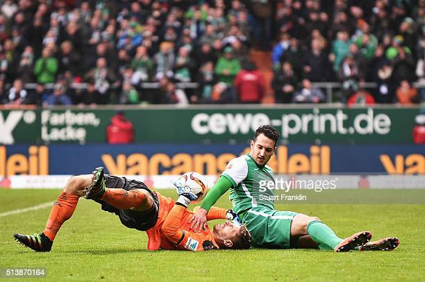 Levin ztunali of Bremen is challenged by RonRobert Zieler of Hannover during the Bundesliga match between Werder Bremen and Hannover 96 at...