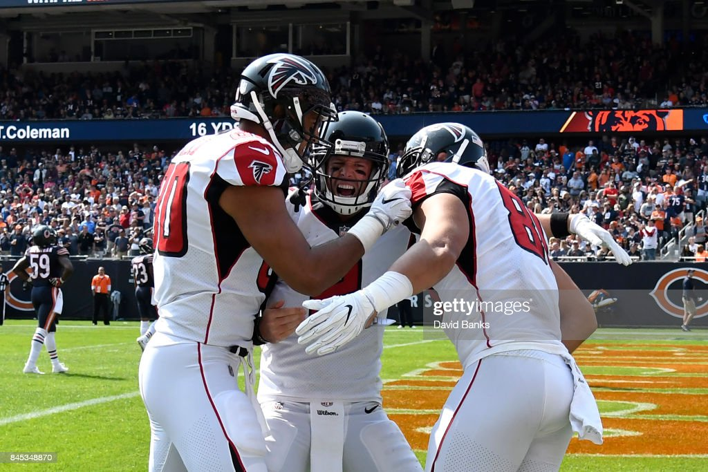 Levine Toilolo #80, quarterback Matt Ryan #2 and Austin Hooper #81 of the Atlanta Falcons celebrate after Hooper scored a touchdown in the fourth quarter against the Chicago Bears at Soldier Field on September 10, 2017 in Chicago, Illinois.