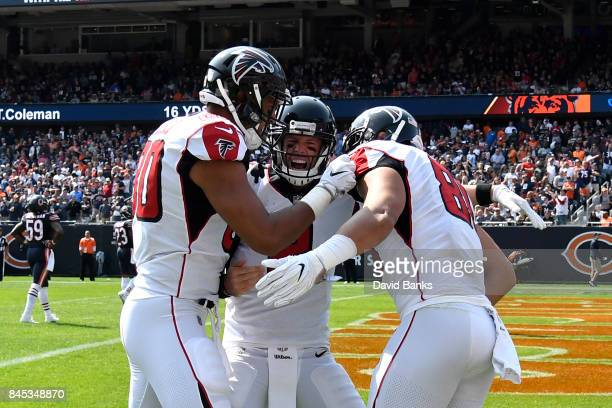 Levine Toilolo quarterback Matt Ryan and Austin Hooper of the Atlanta Falcons celebrate after Hooper scored a touchdown in the fourth quarter against...