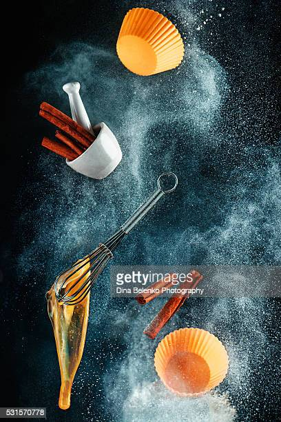 levitating kitchen utensils in a cloud of flour (for cinnamon cupcakes) - slow motion stock pictures, royalty-free photos & images