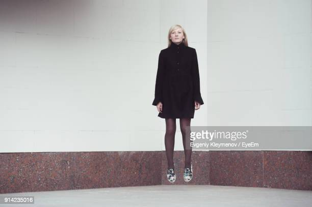 Levitation Of Young Woman Against Wall