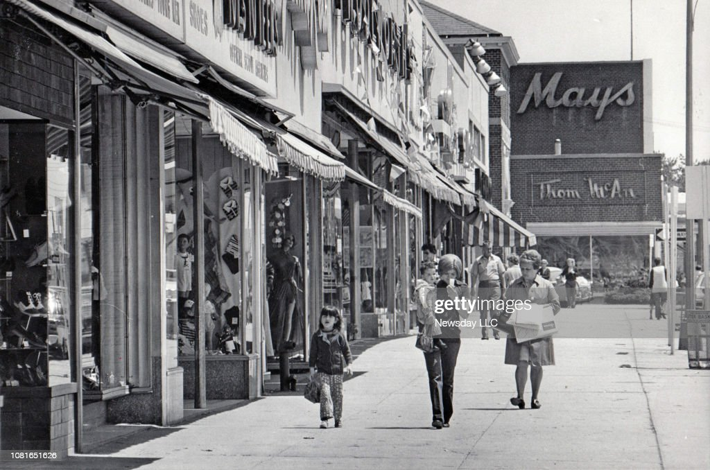 Shoppers walk along Hempstead Turnpike in Levittown, New York on May