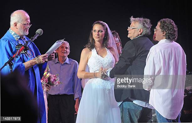 Levon Helm looks on while Jenni Maurer West and Leslie West of Mountain get married onstage during Heros of Woodstock Tour on the 40th anniversary of...