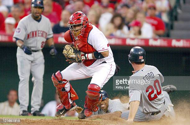 Lew Ford of the Minnesota Twins slides safely into home plate to beat tag of Los Angeles Angels of Anaheim catcher Bengie Molina as Minnesota...