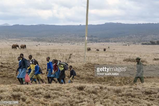 Lewa Wildlife Conservancy ranger Rajimen Lesakut escorts primary school children from nearby MCK Lewa Downs School as they walk across the wildlife...
