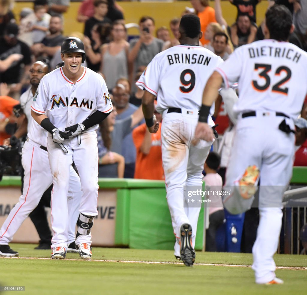 Lewis Brinson #9 and Derek Dietrich #32 of the Miami Marlins run towards Brian Anderson #15 after he hit a sacrifice fly to win the game against the San Francisco Giants at Marlins Park on June 13, 2018 in Miami, Florida.