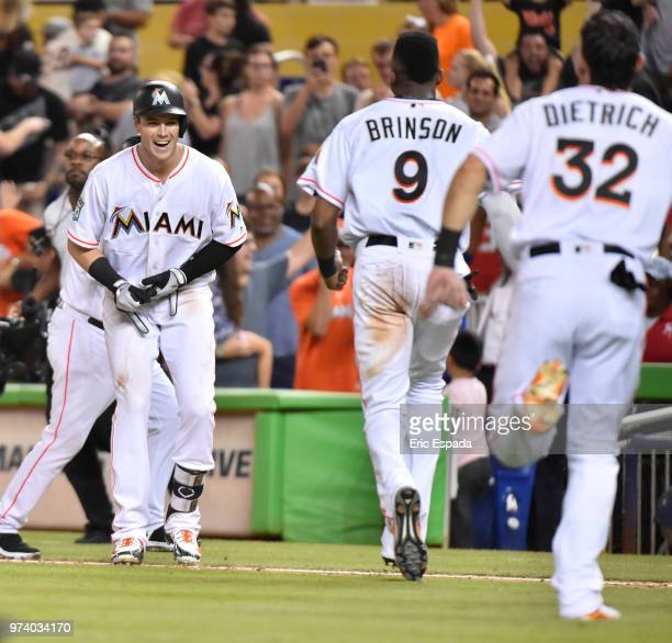 Lewis Brinson and Derek Dietrich of the Miami Marlins run towards Brian Anderson after he hit a sacrifice fly to win the game against the San...